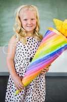 Portrait of smiling schoolgirl holding gift in classroom