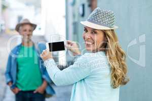 Woman photographing man in city