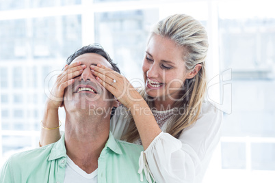 Mid adult woman covering eyes of man