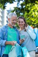 Smiling couple using mobile phone in city