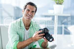 Mid adult man holding camera at home
