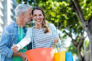 Romantic couple holding shopping bags in city