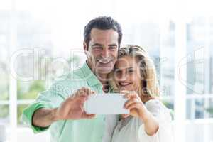 Mid adult couple taking selfie at home