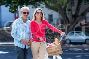 Happy mature couple with bicycle in city