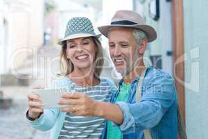 Mature couple taking selfie in city