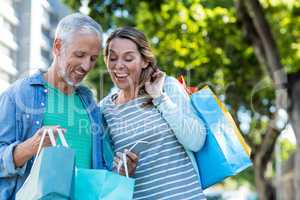 Happy couple with shopping bags in city