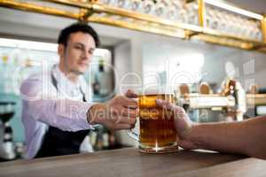 Barkeeper serving beer to customer