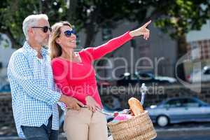 Mature man with woman pointing in city