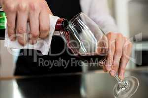 Barkeeper pouring wine in glass