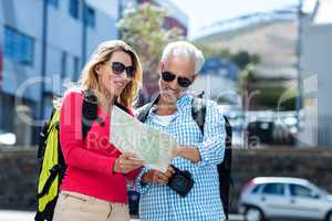 Mature couple reading map in city