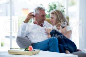 Rose and gift box on table with couple having red wine