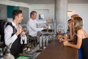 Beautiful women having cocktail while waiter preparing cocktail
