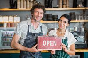 Portrait of waiter and waitress holding open signboard