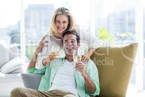 Mid adult couple holding winglasses at home