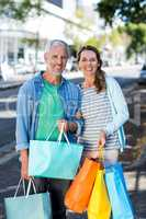 Portrait of couple holding shopping bags in city