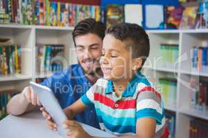 Teacher and school kid using digital table in library