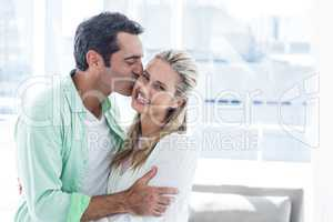 Mid adult man kissing woman at home
