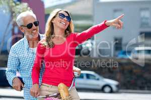 Happy man with woman pointing at city street
