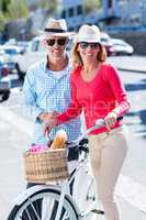 Mature couple with bicycle on city street