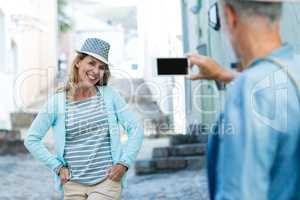 Man photographing smiling woman in city