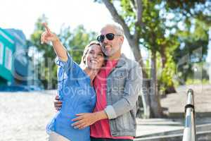 Mature man with woman on footpath in city