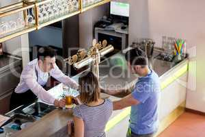 Barkeeper serving beer to couple