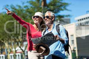 Woman pointing while standing by man in city