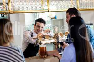 Friends talking to barkeeper while having drinks