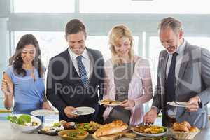 Business colleagues serving themselves at buffet lunch