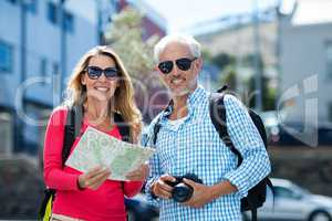 Mature couple holding map and camera in city