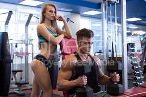 Guy exercising and his girlfriend standing next