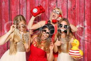 Photo Booth Party mit lustigen Probs - Junge Mädchen albern vor Fotobox herum