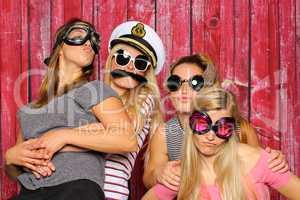 Junge Mädchen mit lustigen Brillen haben Spaß mit einer Fotobox