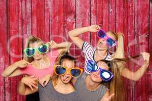 Mädchengruppe mit Brillen albern vor einer Fotobox  herum