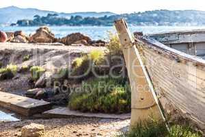 Closeup of aged and abandoned fishing boats laying close to a ri