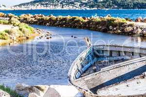 aged and abandoned fishing boats laying close to a river