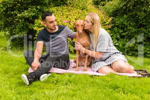 Couple on rug with woman kissing dog