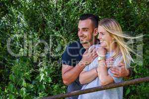 Smiling man hugging blonde girlfriend behind gate