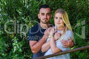 Man holding blonde girlfriend behind iron gate