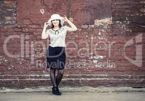 Woman against brick wall