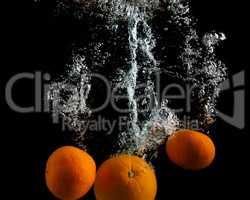 Oranges falling in water