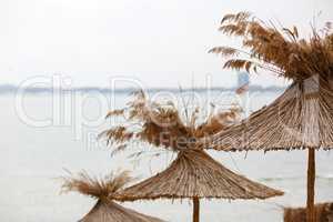 Straw umbrellas on sea background