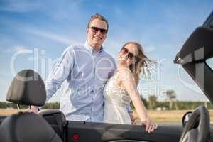 Liebespaar im Urlaubsfieber - Pärchen steht am Cabrio und ist glücklich