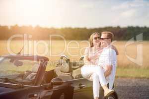 Auf Händen tragen - Mann trägt Frau am Cabrio