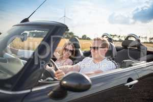 Glückliches Pärchen im Cabrio unterwegs - Mit dem Auto unterwegs
