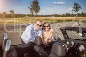 Pärchen lehnt am offenen Cabrio - Urlaubsreise mit dem Cabrio