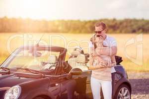 Liebespaar umarmt sich am Auto - Verliebtes Paar am Cabrio