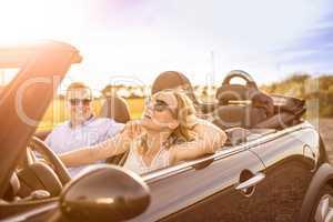 Mit dem Cabrio der Sonne entgegen - Verliebtes Paar lacht im Auto