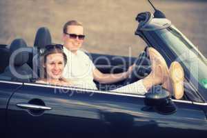 Junge Frau hält lässig ihre Beine aus dem Cabrio
