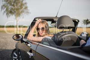 Spritztour im Cabrio - Junge Frau schaut aus einem Cabrio